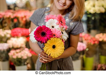 Smiling florist in a grey dress holding a beautiful colorful bouquet of flowers