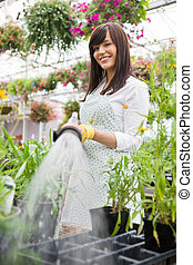 Smiling Florist Watering Plants In Greenhouse
