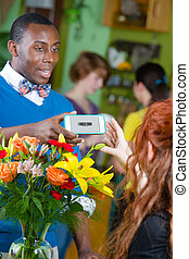 Smiling Flower Shop Customer using Electronic Coupon