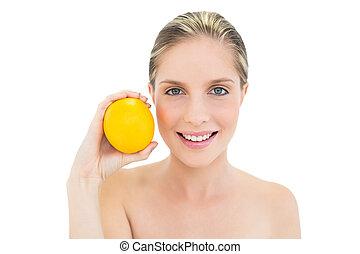 Smiling fresh blonde woman holding an orange