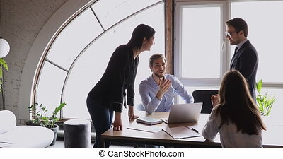 Smiling friendly business team brainstorming in modern office