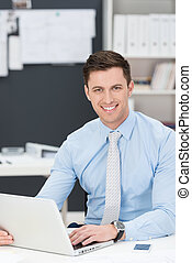 Smiling friendly businessman working on a laptop