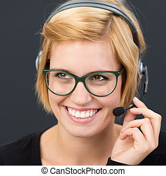 Smiling friendly call centre operator in a headset