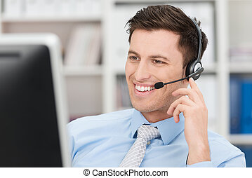 Smiling friendly male call centre operator - Smiling...