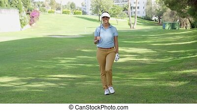 Smiling friendly woman golfer walking on a course - Smiling...