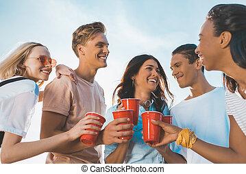 friends clinking plastic glasses