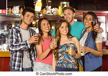 Smiling friends drinking beer and mixed drink