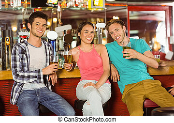 Smiling friends drinking beer together