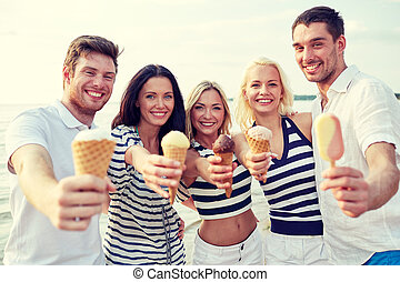 smiling friends eating ice cream on beach