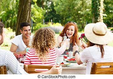 Smiling friends enjoying garden party
