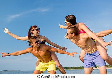 smiling friends having fun on summer beach