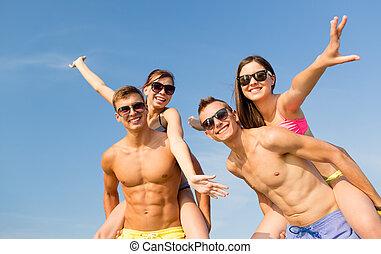 smiling friends having fun on summer beach - friendship,...