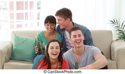 Smiling friends looking at the television while laughing