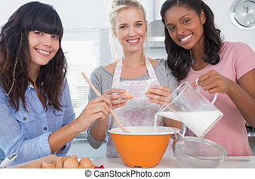 Smiling friends making pastry together looking at camera