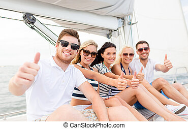 travel, sea, friendship, gesture and people concept - smiling friends sitting on yacht deck and showing thumbs up