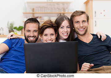 Smiling friends sharing a laptop computer