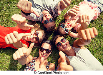 smiling friends showing thumbs up lying on grass -...