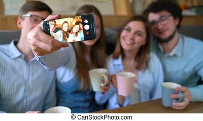 Smiling friends sit in a cafe, have fun communicating and make selfie. Slow motion