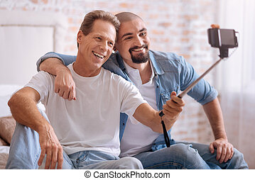 Smiling friends taking selfie at home