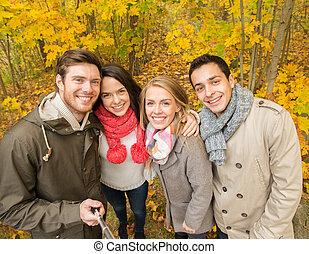 smiling friends taking selfie in autumn park