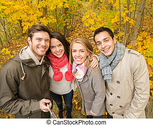 smiling friends taking selfie in autumn park - season,...