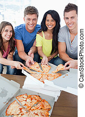Smiling friends taking some pizza as they look at the camera