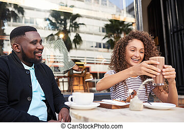 Smiling friends talking together over coffee at a sidewalk cafe