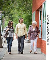 Smiling Friends Walking On Pavement