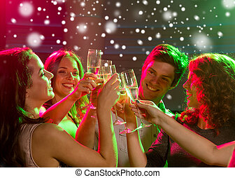 smiling friends with glasses of champagne in club