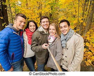 smiling friends with smartphone in city park - season,...