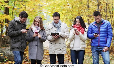 smiling friends with smartphones and tablet pc