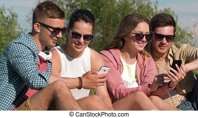smiling friends with smartphones in summer park -...