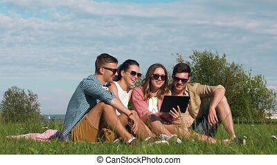 smiling friends with tablet pc sitting on grass
