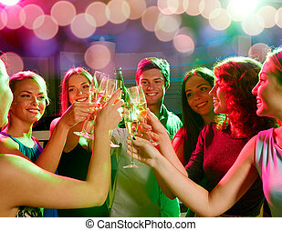 smiling friends with wine glasses and beer in club