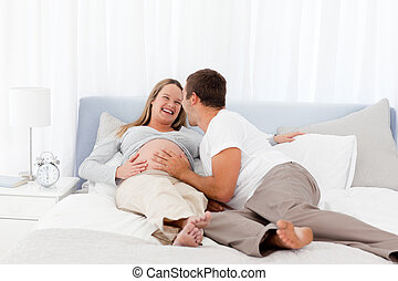 Smiling future parents liyng on the bed