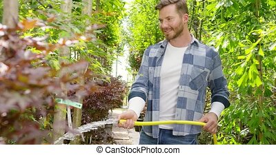 Smiling gardener with hose - Cheerful man doing horticulture...