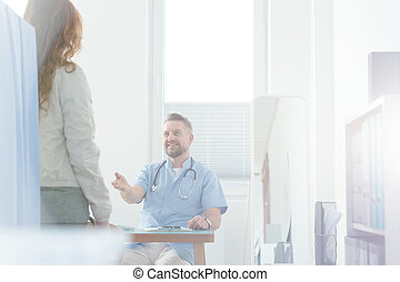 Smiling general practitioner welcoming patient in the clinic