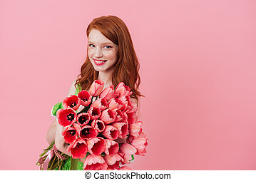 Smiling ginger woman holding bouquet of flowers