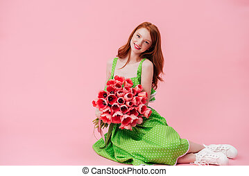 Smiling ginger woman sitting on floor with bouquet of flowers