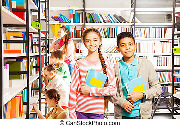 Smiling girl and boy in library with books