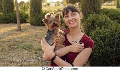 Smiling girl and small dog Yorkshire terrier posing outdoors.