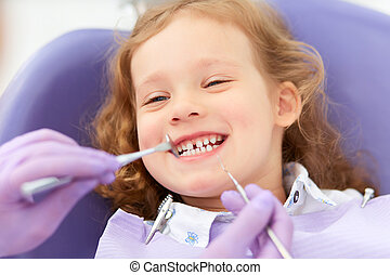 Smiling girl at dentist - Hands of unrecognizable pediatric...