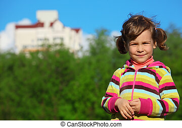 smiling girl at field against the home