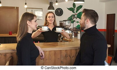 Smiling girl Barista giving drink to a couple sitting near bar counter in cafe