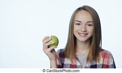 Smiling girl biting big green apple