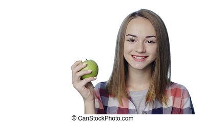 Smiling girl biting big green apple