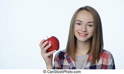 Smiling girl biting big red apple