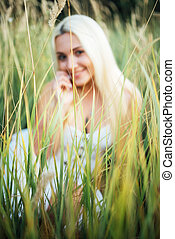 smiling Girl blonde sitting in tall grass in background blurred.