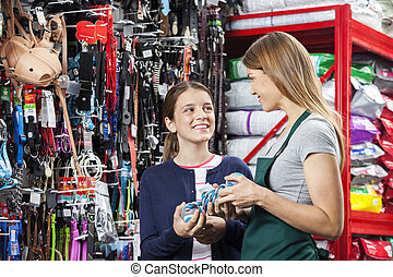 Smiling Girl Buying Toy From Saleswoman In Pet Store -...