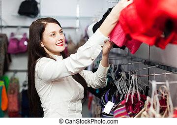 Smiling girl choosing bra at fashion store